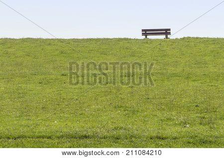 coastal scenery with wooden bench on a dam around Buesum in Dithmarschen at Schleswig-Holstein Germany