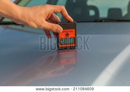 inspection of the body and bonnet of the car, the man measures the car's body with the appliance, car painting quality control