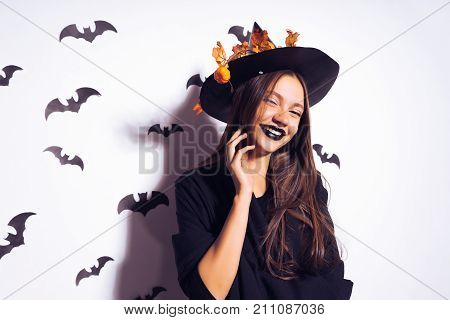 a young gothic sexy gothic girl celebrates halloween, in the image of a witch, on her head a big black hat adorned with yellow autumn leaves