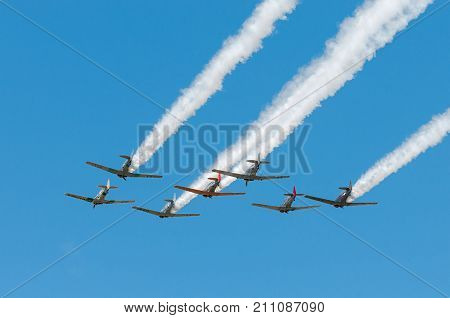 EDEN PRAIRIE MN - JULY 16 2016: Seven AT-6 Texan planes fly away trailing smoke at air show. The AT-6 Texan was primarily used as trainer aircraft during and after World War II.