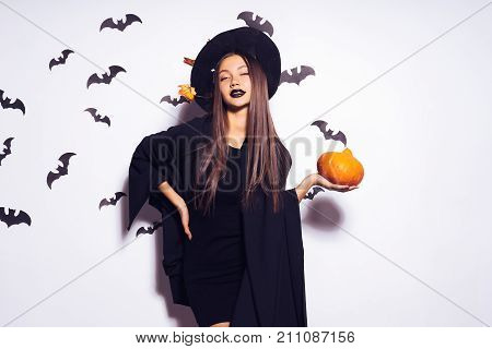 a young gothic sexy gothic girl celebrates halloween, in the image of a witch, on her head a big black hat decorated with yellow autumn leaves holds a pumpkin in her hands