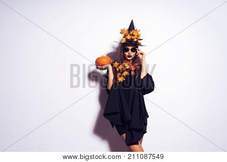 a young, gothic sexy gothic girl celebrates halloween, in the image of a witch, on her head a big black hat decorated with yellow autumn leaves holds a pumpkin