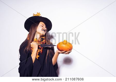 a young gothic sexy gothic girl celebrates halloween, in the image of a witch, on her head a big black hat, adorned with yellow autumn leaves, keeps a pumpkin and a knife