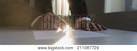 Panorama View Of Businessman In A Shadowy Office Signing Contract