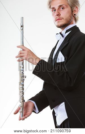 Classical music study concept. Male flutist musician performer playing flute. Young elegant man wearing tailcoat holds instrument