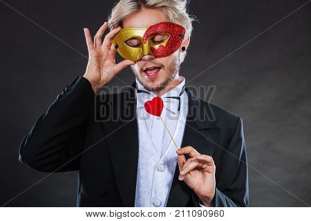 Valentines day. Love concept. Holidays and celebration. Elegant young guy wearing suit white shirt bow tie with carnival mask and heart stick in hand on dark.