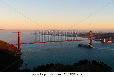 Container ship passing under the Golden Gate bridge at sunset portraying the importation of everything from China