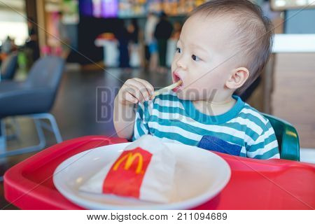 Bangkok THAILAND - October 21 2017: Cute Asian toddler baby boy sitting in high chair eating french fries at McDonald's restaurant McDonald's is American fast food restaurant chain Selective focus
