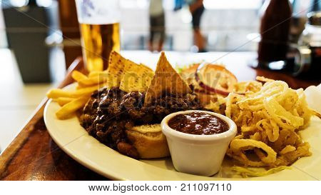 Unhealthy meal with mexican nacho chips loaded with beef, cheese, fries, onion rings and hot souse