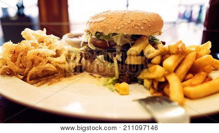 Unhealthy meal with mexican nacho chips, beef burger, loaded with cheese, fries, onion rings and hot souse
