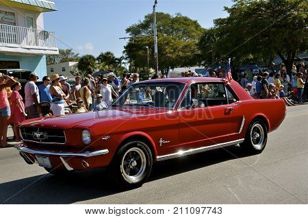 FORT MYERS BEACH, FLORIDA, March 13, 2015:  The red restored 1966 Ford Mustang is part of the parade sponsored each year by the Lions Club at the Shrimp Festival attended by thousands for the 5k run, parade, and craft show with shrimp food booths.