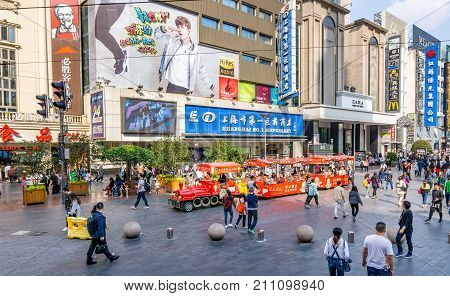 Shanghai, China - Nov 6, 2016: View of Nanjing Road Pedestrian Street - Modern buildings in western architectural designs line the metropolitan area. Shot from a public bus. Feature numerous activities.