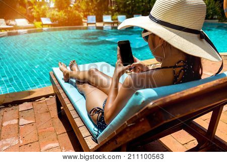 Bikini woman sexy in pool relaxing young asian beautiful female resting in vacation on summer season with hat at resort swimming pool edge with chair beach on side with holding phone