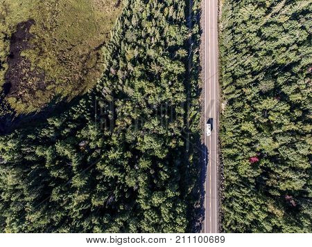 Canada beautiful scenic camper bus driving on road in the endless pine tree forest with lakes moor land , aerial view travel background