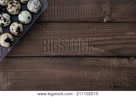 Some quail eggs on the brown wooden table