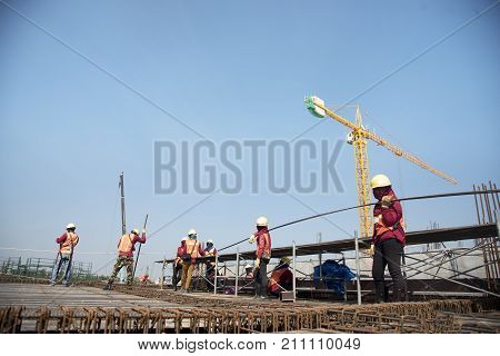 workers hands using steel wire and pincers to secure rebar before concrete is pour over it Construction site worker