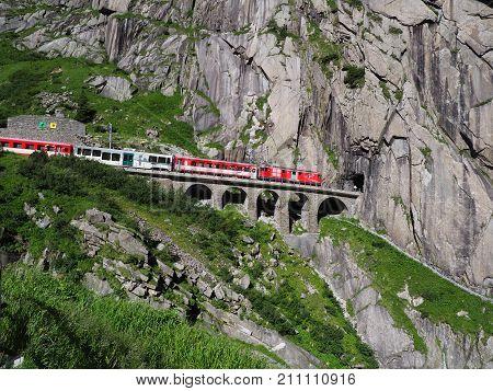 ANDERMATT SWITZERLAND EUROPE on JULY 2017: Express St. Gotthard train on Teufelsbruecke Devil's railway bridge and tunnel swiss Alps alpine rocky mountains landscape scenery in warm summer day.