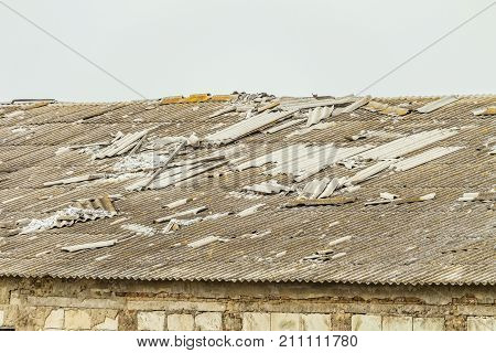 Old collapsing asbestos-cement roof of a dilapidated agricultural building