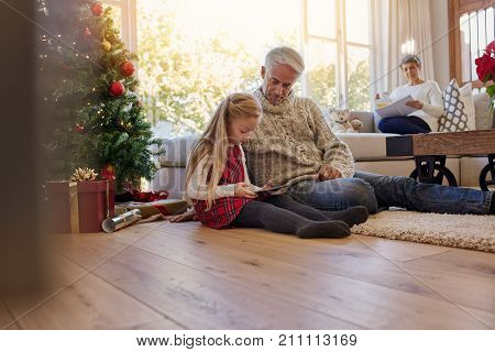 Little girl with grandfather sitting on floor and using digital tablet during Christmas with grand mother sitting on sofa at the back. Little girl and grand parents in living room during christmas.