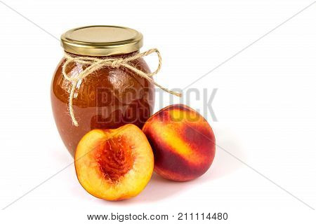 Fruit jam jar. Wallpaper with homemade nectarine jam in a glass jar and fresh peaches