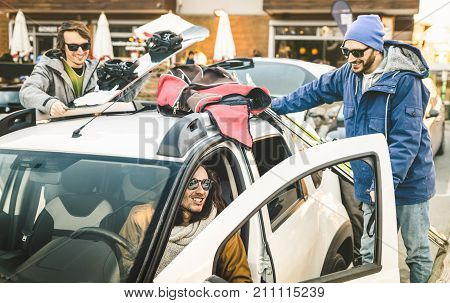 Best friends having fun together preparing car for ski and snowboard at mountain trip - Friendship hangout concept with young people loving winter sports travel - Vintage desaturated contrast filter