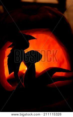 Halloween pumpkin lantern with carved devilish girl