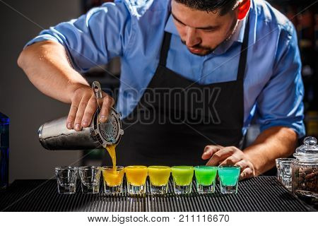 Barman is preparing Rainbow color shots, close up