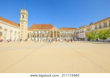 Coimbra, Portugal - August 14, 2017: tourists inside courtyard of Patio das Escolas and the Clock Tower of University of Coimbra, the most ancient of Portugal and also one of the oldest in Europe.