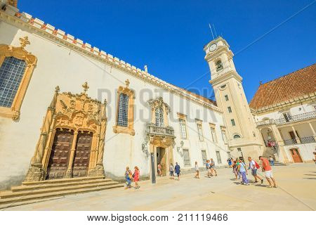 Coimbra, Portugal - August 14, 2017: people visit University of Coimbra, one of oldest universities in the world. Iconic Clock Tower in blue sky. Unesco Heritage and most important tourist attraction.