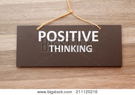 Word POSITIVE THINKING written on chalkboard hang on the wooden wall