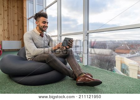 Hispanic Business Man Using Tablet Computer Sit In Front Panoramic Window Happy Smiling Businessman Coworking Center Office Interior