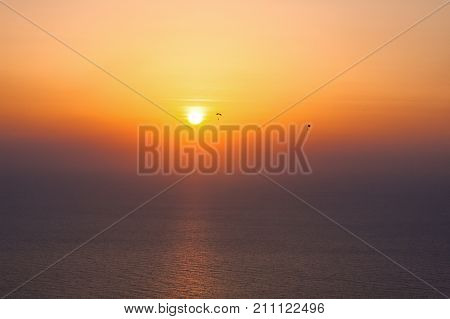 Parachute jump during sunset. Silhouette of parachutists over the ocean. Coloured sunset in Dubai United Arab Emirates