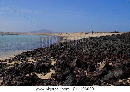 Volcanic rocks at tourists at Lobos Beach, on inhabited island Lobos, Fuerteventura, Spain