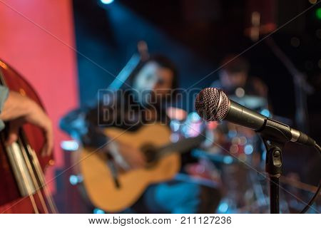 Acoustic trio band performing on a stage in a nightclub with the microphone in focus waiting for its singer