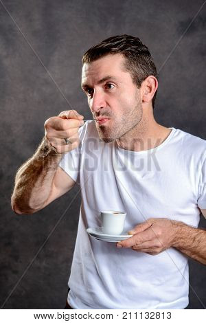 young dark haired in white shirt man drinking espresso