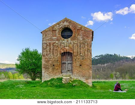 A Couple Relaxing Near An Abandoned Chapel Next To The Abbey Of San Galgano In Chiusdino