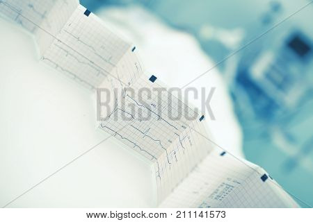 Folded ECG trace in the background of patient bed.