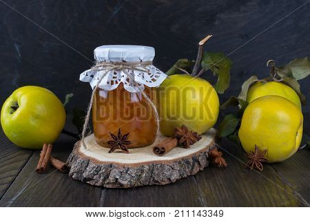 Quince jam in glass jar and fresh quince with leaves selective focus on dark wooden table.