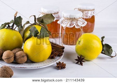 Quince jam in glass jar and fresh quince with leaves selective focus on white wooden table.