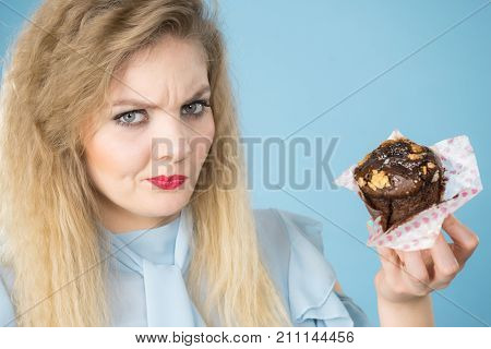 Skeptical Woman Holding Chocolate Cupcake Muffin