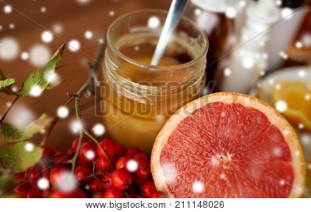healthcare, traditional medicine and ethnoscience concept - grapefruit, honey with rowanberry and drugs over snow
