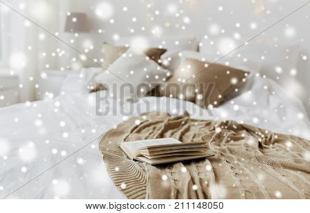 cosy home and winter concept - book on bed in bedroom at christmas over snow