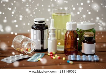 healthcare, medicine and drugs concept - pills, nasal spray, antipyretic syrup and glass on wooden table over snow