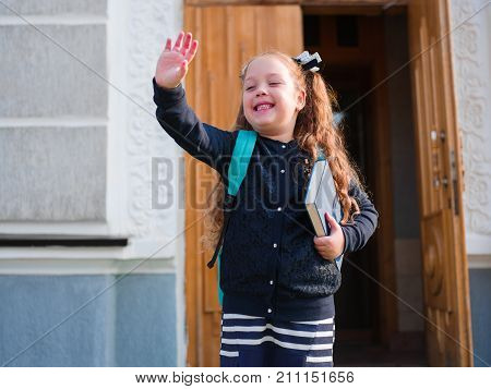 A girl goes to school with a briefcase and a book waving her hand good-bye
