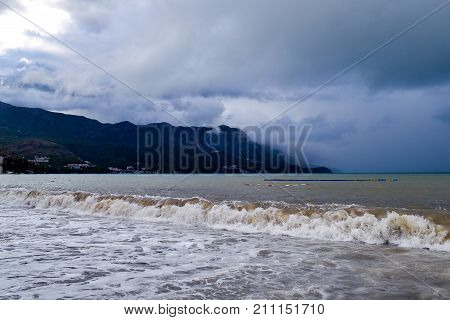 Low clouds over the coast. Waves of turbid water. Montenegrin beach in rainy weather. The sea and mountains of Montenegro. Budva. Becici