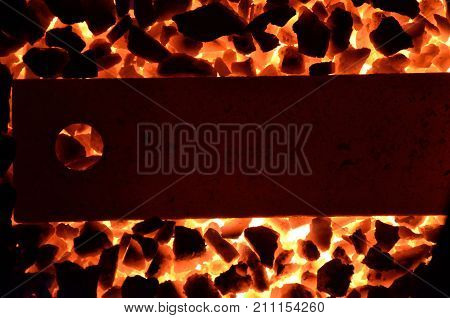 Background of burning coal anthracite and a red-hot steel strip.