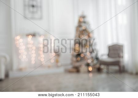Unfocused classic white christmas interior with new year tree decorated. Fireplace with grey chair, clocks on the wall and presents under the tree