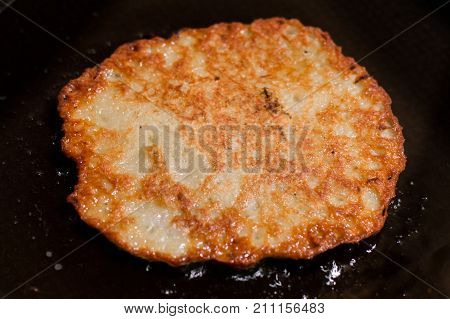 Frying potato pancakes, latkes or boxties on black pan.