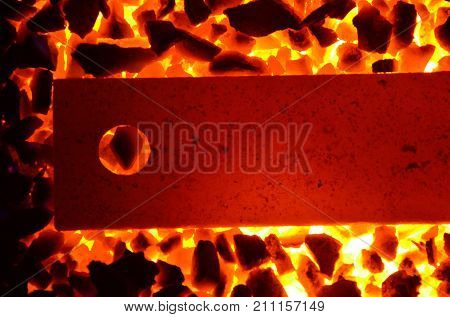 Background of burning coal anthracite and a red-hot steel strip with a hole.
