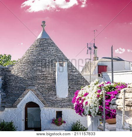 Typical Trullo of Alberobello with rose sky background